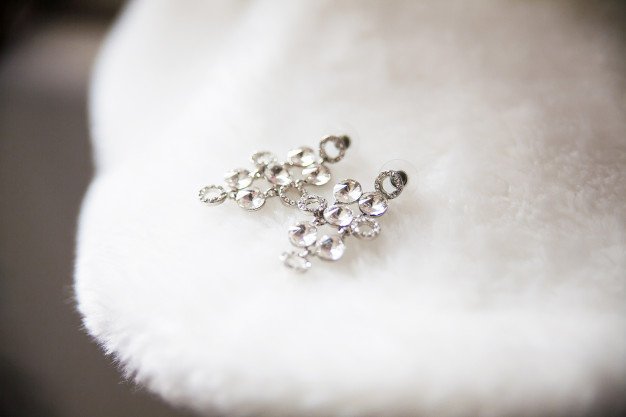 bride-earrings-lie-white-cape-closeup_127746-295