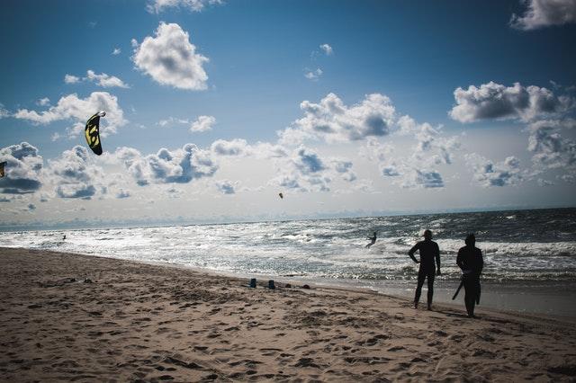 Dvaja ľudia stojaci na pláži počas západu slnka.jpg
