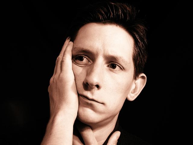Zamyslený muž, depresia, tmavé pozadie.jpg