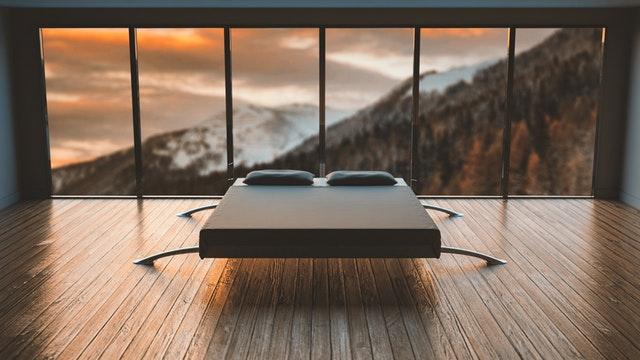 Posteľ v spálni so sklenenou stenou
