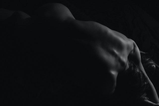 Chrbát nahej ženy v tme